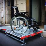 oprijplaat-met-platform-en-wieltjes-bij-winkel-met-rolstoel